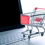 Miniatur-Einkaufswagen auf einem Laptop